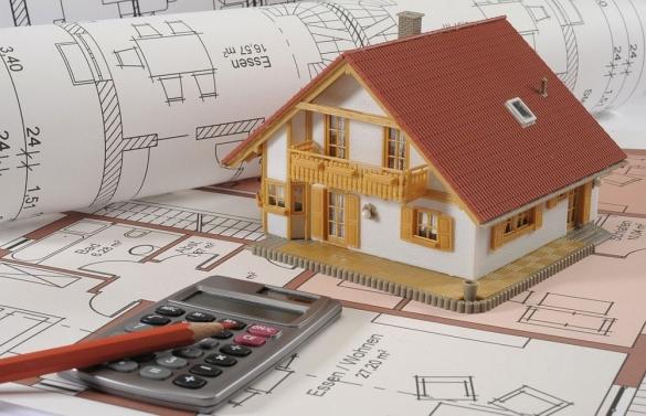 Фото на тему экономии в строительстве: модель дома на фоне калькулятора