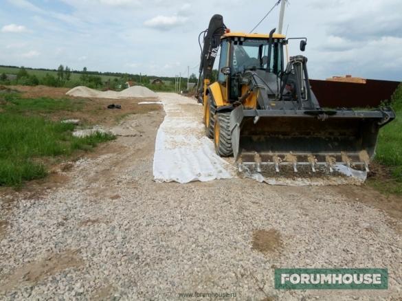 Фото бульдозер планирует подъездную дорогу гравием поверх геотекстиля